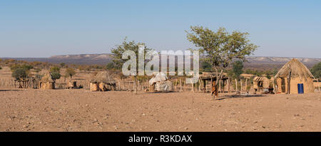 Thatched huts of a Himba village on a plateau near Opuwo, Namibia. - Stock Photo