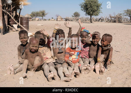 Dusty young children of the village sit to have some fun in the dirt, in a Himba village near Opuwo, Namibia. - Stock Photo
