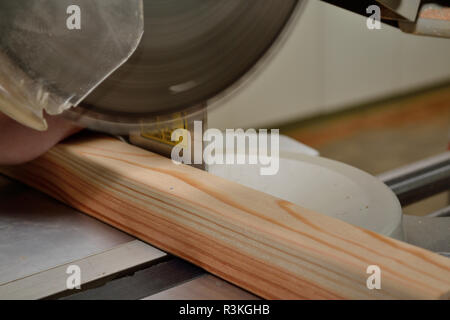 durchsaegen with chop saw holzstueck - Stock Photo