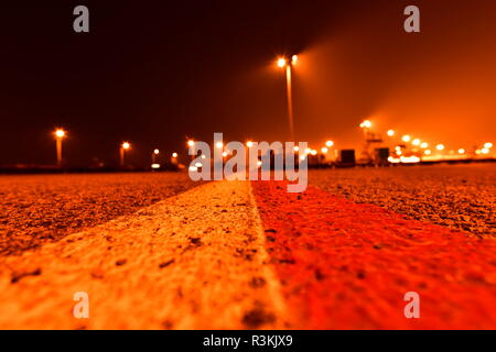 Red white marking line on asphalt in plane parking area at Airport. Blurred lights in the background. Narrow depth of field. - Stock Photo