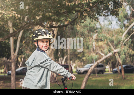 Australian boy riding bicycle on special bike track in Adelaide, South Australia - Stock Photo