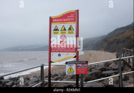 Beach safety sign at the famous Jurassic coast beach between Charmouth and Lyme Regis in West Dorset UK - Stock Photo