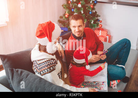 Merry Christmas and Happy New Year. Lovely picture of family sitting together on sofa. Parents look at each other. Woman wears hat. Young man smiles.  - Stock Photo