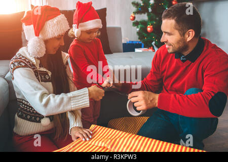 Nice picture of family preparing gifts together. Girl and young man holds tape together. Woman cut it with scissors. They look nice and positive - Stock Photo