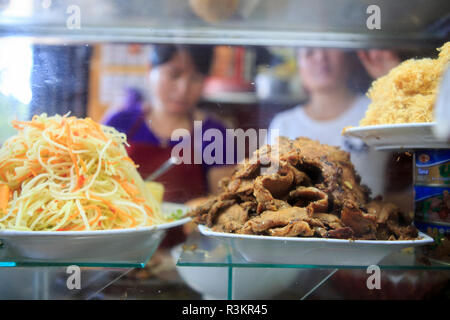Banh Mi Phuong workers preparing the traditional food from ingredients in a glass case. Hoi An, Vietnam - Stock Photo