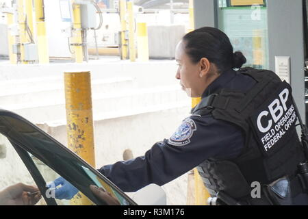 A U.S. Customs and Border Patrol agent returns identification to a driver entering the United States from Mexico at the San Ysidro crossing November 22, 2018 in San Ysidro, California. - Stock Photo