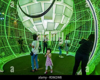 November 23, 2018 - Bangkok, Bangkok, Thailand - A child walks through a lit ball, that represents an ornament, in the ''World of Happiness,'' the Christmas display at Central World, a large mall in Bangkok. Although Thailand is an overwhelmingly Buddhist country, the commercial aspects of Christmas are widely observed, especially in Thailand's urban areas, which have large concentrations of Europeans and Americans. (Credit Image: © Jack Kurtz/ZUMA Wire) - Stock Photo
