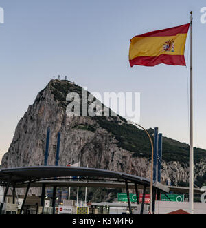 23 November 2018, Spain, La Linea de la Conception: A Spanish flag is flying at the border crossing between the Spanish La Linea de la Conception and Gibraltar. Behind it you can see the rock of Gibraltar. After the broad agreement between Britain and the European Union, Gibraltar - the monkey rock - is one of the last stumbling blocks before the conclusion of a comprehensive Brexit agreement on Sunday. Photo: Frank Rumpenhorst/dpa - Stock Photo