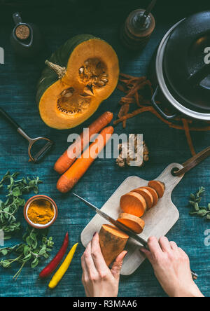 Female hands cooking healthy soup or vegetables stew with orange color vegetarian ingredients : pumpkin, carrots, sweet potatoes , turmeric, ginger an - Stock Photo