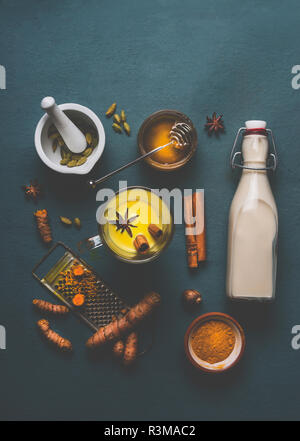 Cup of golden turmeric milk with ingredients: cardamom