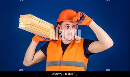 Carpenter, woodworker, labourer, builder carries wooden beam on shoulder. Protective equipment concept. Man in protective gloves holds visor of helmet - Stock Photo