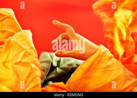 One beautiful wooden hand making a  token gesture , a vibrant yellow and green  cloth  surrounds  the hand , the background is red and out of focus - Stock Photo