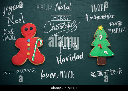 homemade cookies in the shape of a candy cane and a christmas tree, and the text merry christmas in different languages, such as german, czech, japane - Stock Photo
