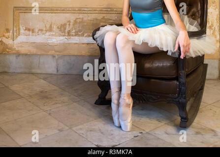 Cuba, Havana. Close-up of ballerina sitting on antique leather rocker. Credit as: Wendy Kaveney / Jaynes Gallery / DanitaDelimont.com - Stock Photo