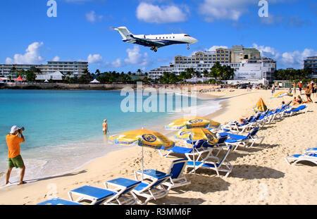 St. Martin, Netherland Antilles, Maho Beach. Private jet landing over the beach in St. Maarten - Stock Photo