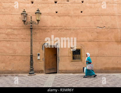 Woman walks along clay walls of Badi Palace in Marrakech (Marrakesh), Morocco