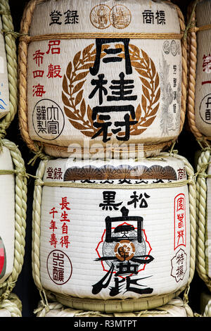 Kobe, Japan. Barrels of Sake wrapped in straw at the entrance to Ikuta Jinja Temple, as an offering - Stock Photo