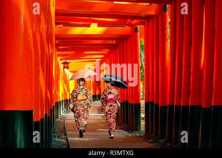 Kyoto, Japan. Two women in kimono walk along the torii gate path of Fushimi Inari Taisha shrine - Stock Photo
