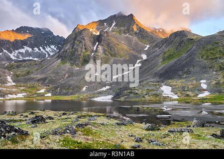 Early morning in mountain tundra in summer. Sunlight illuminates mountain ridge with a golden color through a cloudy haze. Eastern Siberia. Russia - Stock Photo