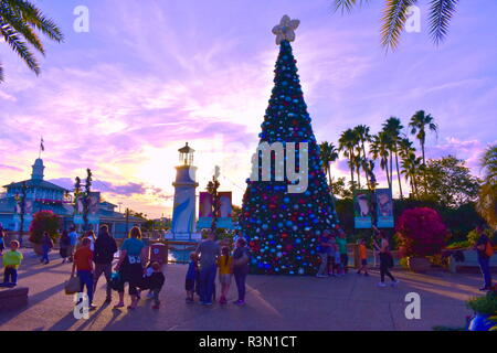 Orlando, Florida. November 17, 2018. People walking out of the park, near decorated christmas tree on sunset background in International Drive area. - Stock Photo