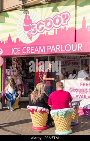 People sat outside Scoop, a Blackpool Ice cream parlour on the promenade at Blacvkpool Lancashire England UK GB Europe - Stock Photo
