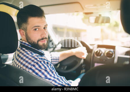 Handsome elegant serious man drives a car - Stock Photo