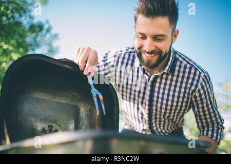 Handsome man preparing barbecue for friends. man cooking meat on barbecue - Chef putting some sausages and pepperoni on grill in park outdoor - Concep - Stock Photo