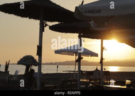 Sunset at the beach in Spain, parasols, sea - Stock Photo