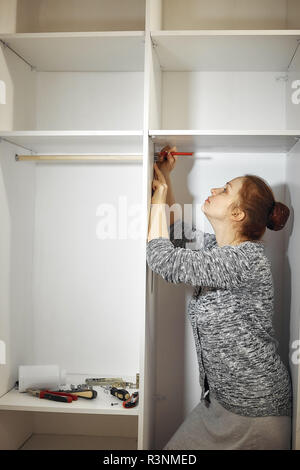 collects furniture in the room Caucasian middle-aged woman - Stock Photo