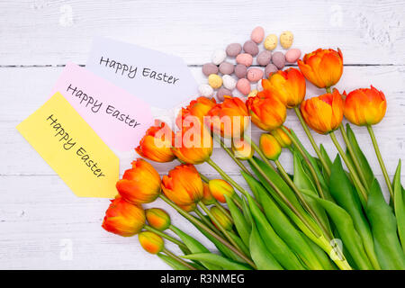 A bunch of tulips with easter eggs on a wood background with a Happy Easter message - Stock Photo