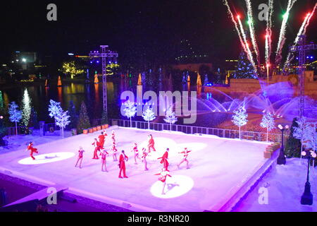 Orlando, Florida. November 19, 2018. Artist group skating at Christmas Show on ice on colorful background with fireworks in International Drive area. - Stock Photo