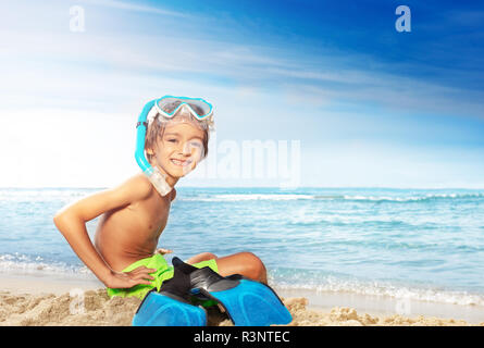 Happy little diver sitting on the sandy beach - Stock Photo