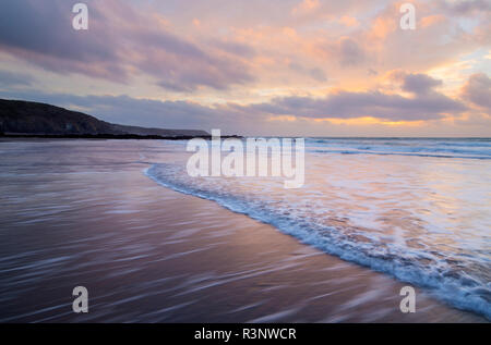 Sunrise over Kennack Sands on the Lizard Coast of Cornwall - Stock Photo