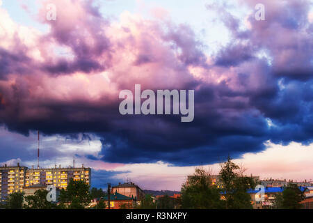 Ominous and foreboding blue grey storm clouds moving in over the city. Image of an impending thunderstorm - Stock Photo