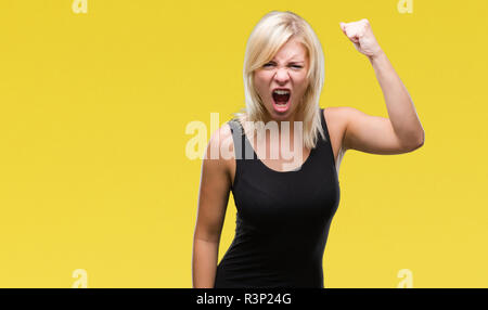 Young beautiful blonde attractive woman wearing elegant dress over isolated background angry and mad raising fist frustrated and furious while shoutin - Stock Photo