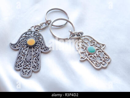 Two key rings in the form of Fatima Hand on a white silk background. Ancient symbol and traditional modern tourist souvenir of Tunisia. - Stock Photo