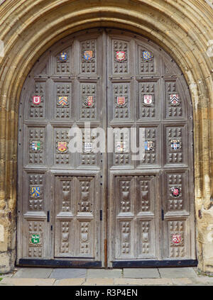 The great gate to the European library or Bodleian library great gate in Oxford part of the university in Britain with traditional crests or shields - Stock Photo