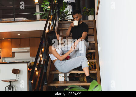 Couple interacting with each other while having coffee in stairs - Stock Photo