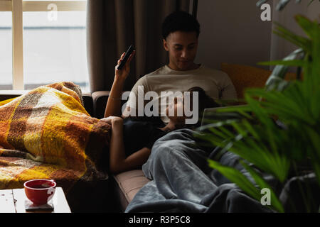 Couple using mobile phone on sofa in living room