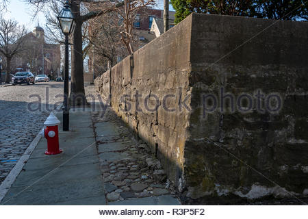 New Bedford, Massachusetts, USA - April 14, 2018: Old stone wall and cobblestones on Bethel St. with New Bedford Whaling Museum in background - Stock Photo