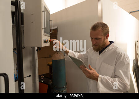 Robotics engineer using digital tablet while controlling control panel - Stock Photo