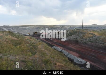A large coal mining truck transports coal inside an open pit coal mine in the Powder River Basin of Wyoming, USA. - Stock Photo