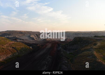 Lone vehicle driving through an open pit coal mine in the Powder River Basin, Wyoming / USA. - Stock Photo