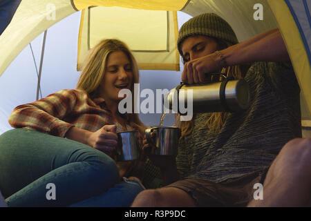 Couple having coffee in tent - Stock Photo