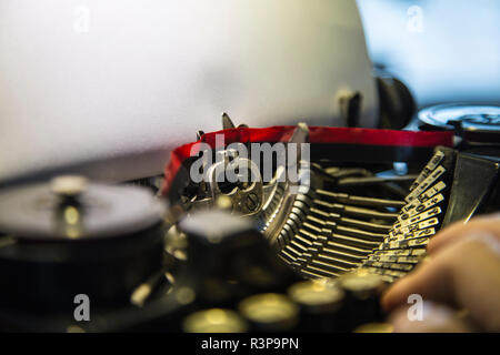 ancient old typewriter with a blank sheet and tip hand - Stock Photo