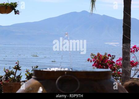 Fuente de vasija en Chapala, Jalisco, Mexico foto tomada a medio dia  en la que aparece en primer plano la fuente, en segundo plano unas flores - Stock Photo