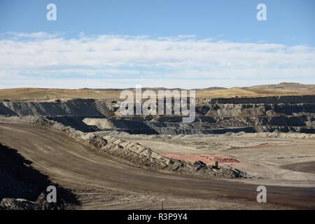Panorama of an empty, vast, deep open pit coal mine landscape in the Powder River Basin, Wyoming, USA. - Stock Photo
