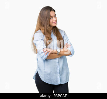 Young beautiful brunette business woman over isolated background smiling looking to the side with arms crossed convinced and confident - Stock Photo