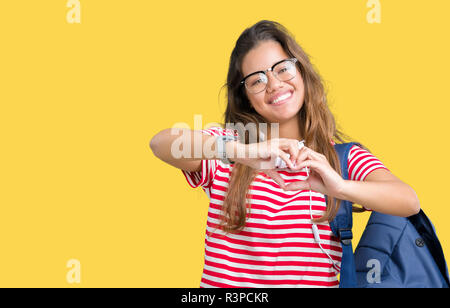 Young beautiful brunette student woman wearing headphones and backpack over isolated background smiling in love showing heart symbol and shape with ha - Stock Photo