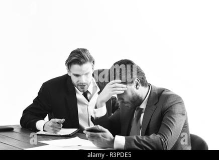 Financial crisis, credit debt, bankruptcy. Men in with tired, worried faces read business news. Business partners in formal suits look at smartphone.  - Stock Photo